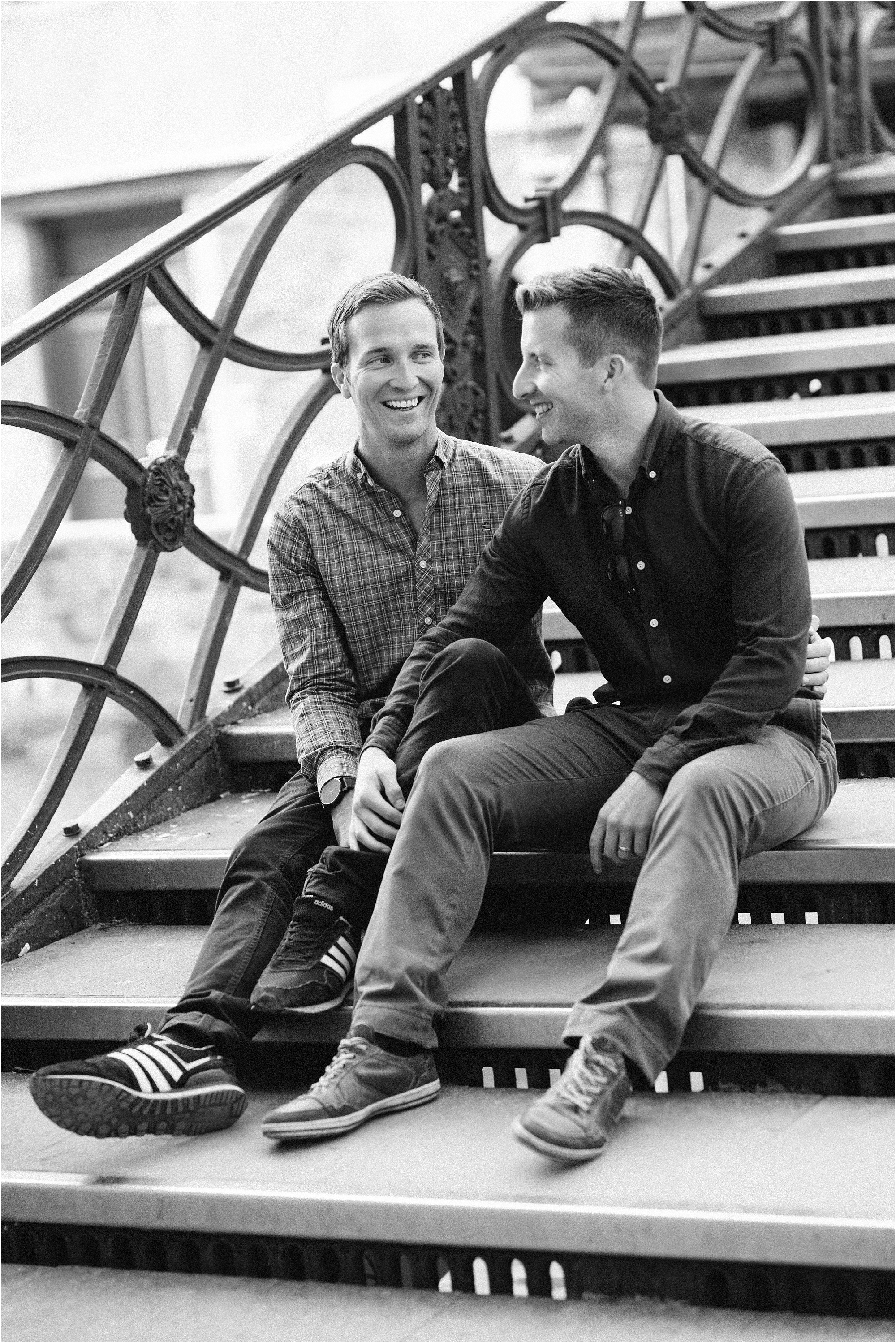 Male gay couple sitting on Venice bridge