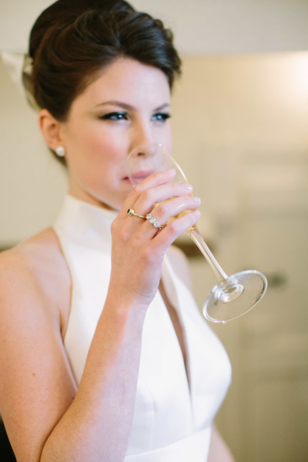Bride drinking champagne on the morning of her Goodwood House wedding