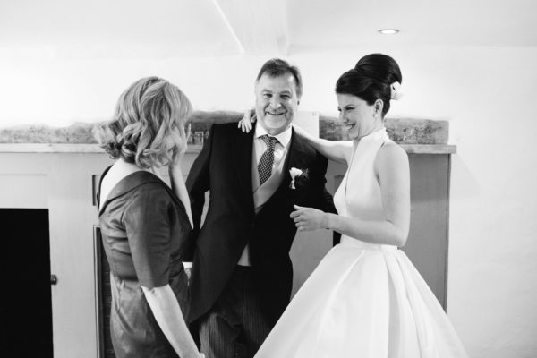 Bride smiling with her mother and father on the morning of her wedding