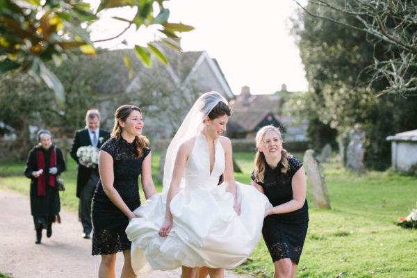 Bride walking to Boxgrove Priory holding up her wedding dress