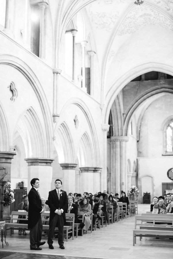 Black and white photograph of groom waiting with best man at the alter of Boxgrove Priory