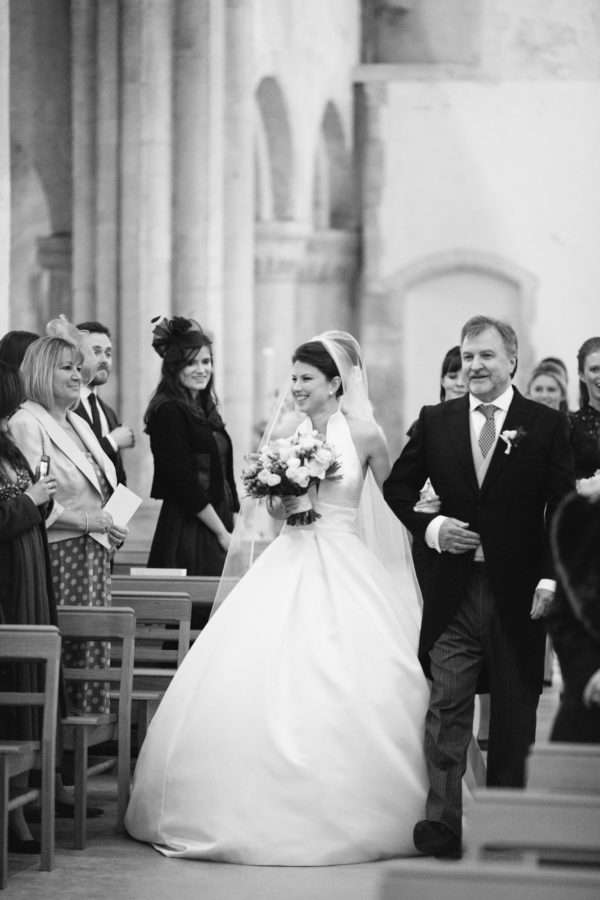 Bride and father of the bride walking up the aisle of Boxgrove Priory wedding