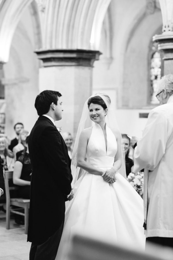 Bride and groom smiling at each other during wedding ceremony at Boxgrove Priory