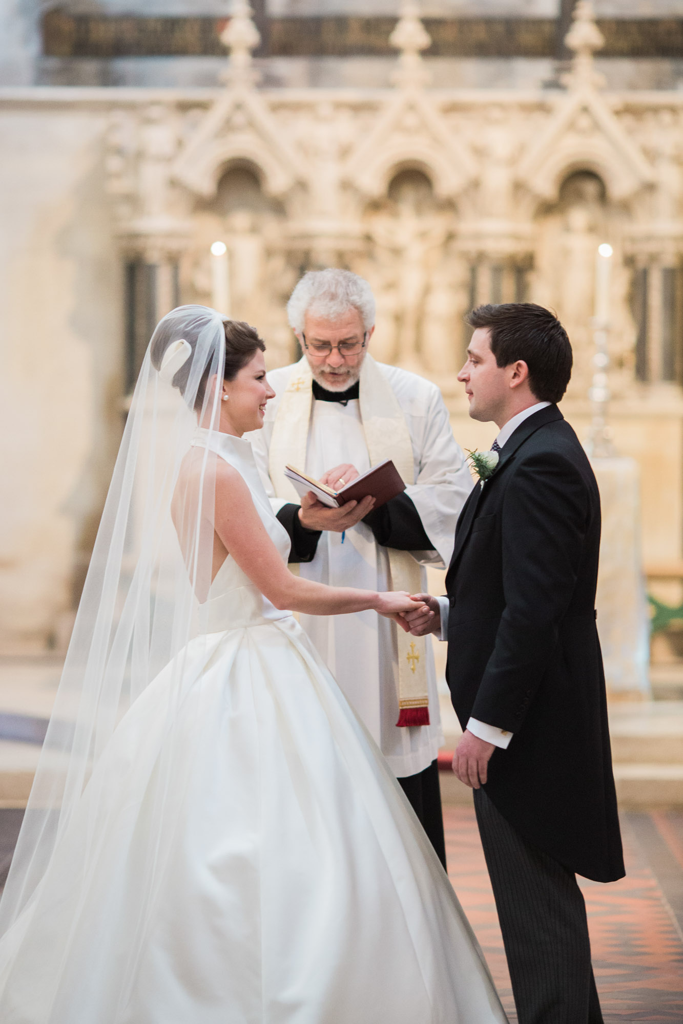 Bride and groom exchanging wedding vows in Boxgrove Priory