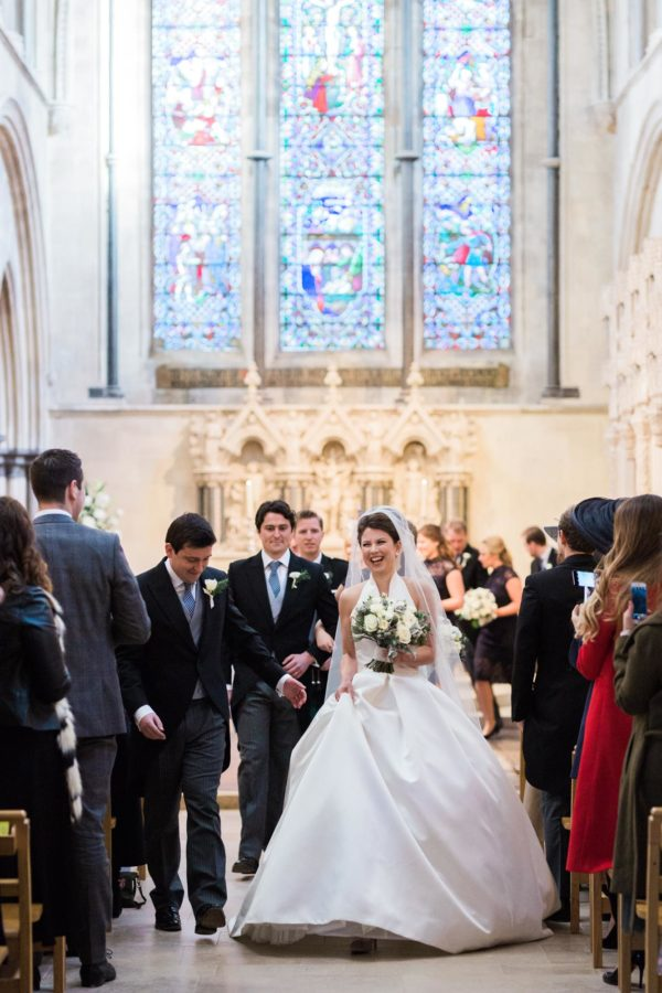 Bride and groom walking down the aisle smiling after their wedding ceremony at Boxgrove Priory