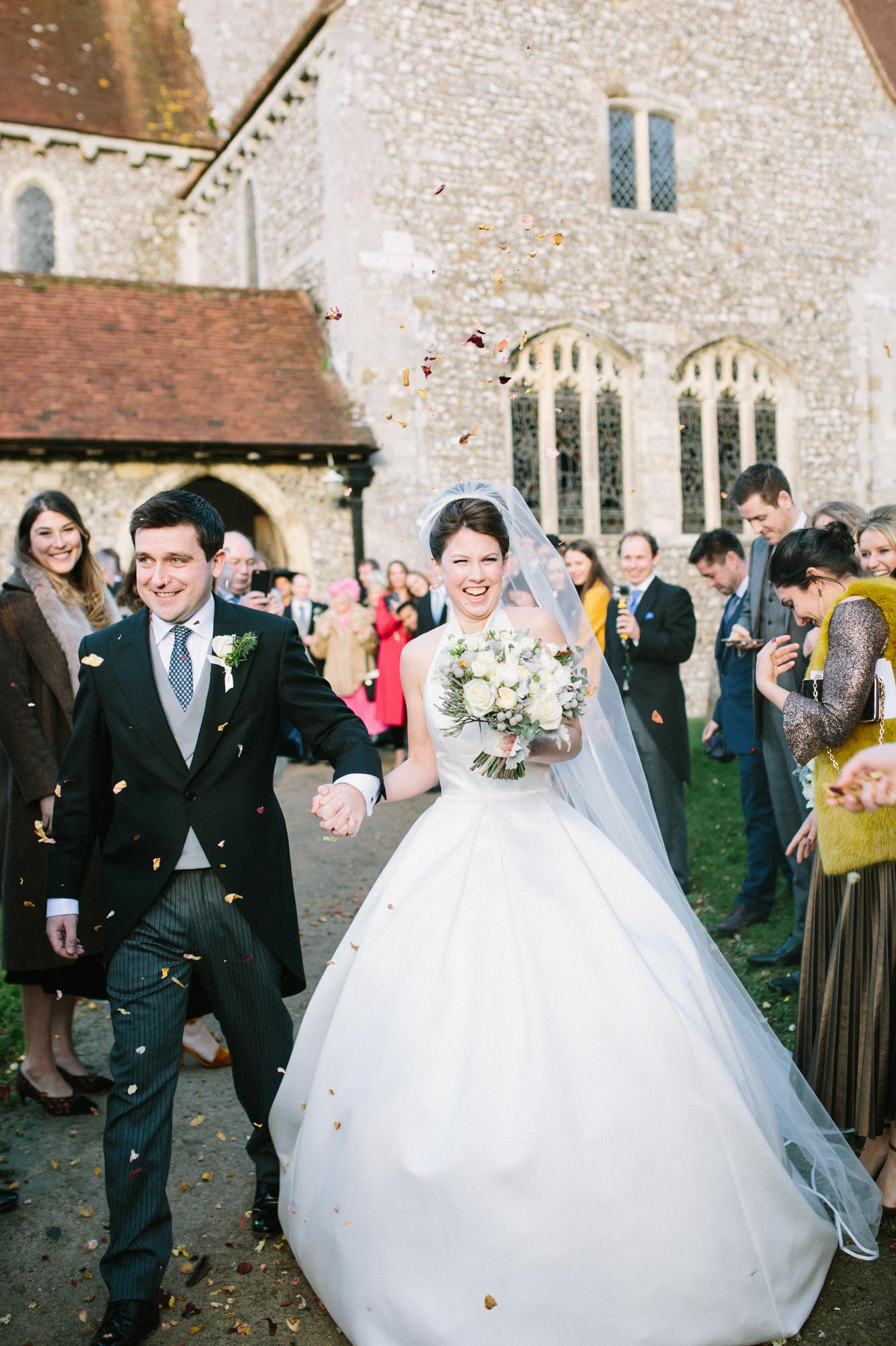 Bride and groom smiling happily and walking through confetti at Boxgrove Priory
