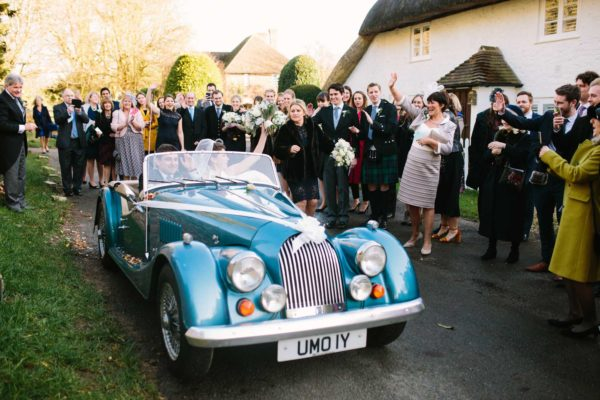 Bride and groom leaving Boxgrove Priory in blue convertible vintage wedding car