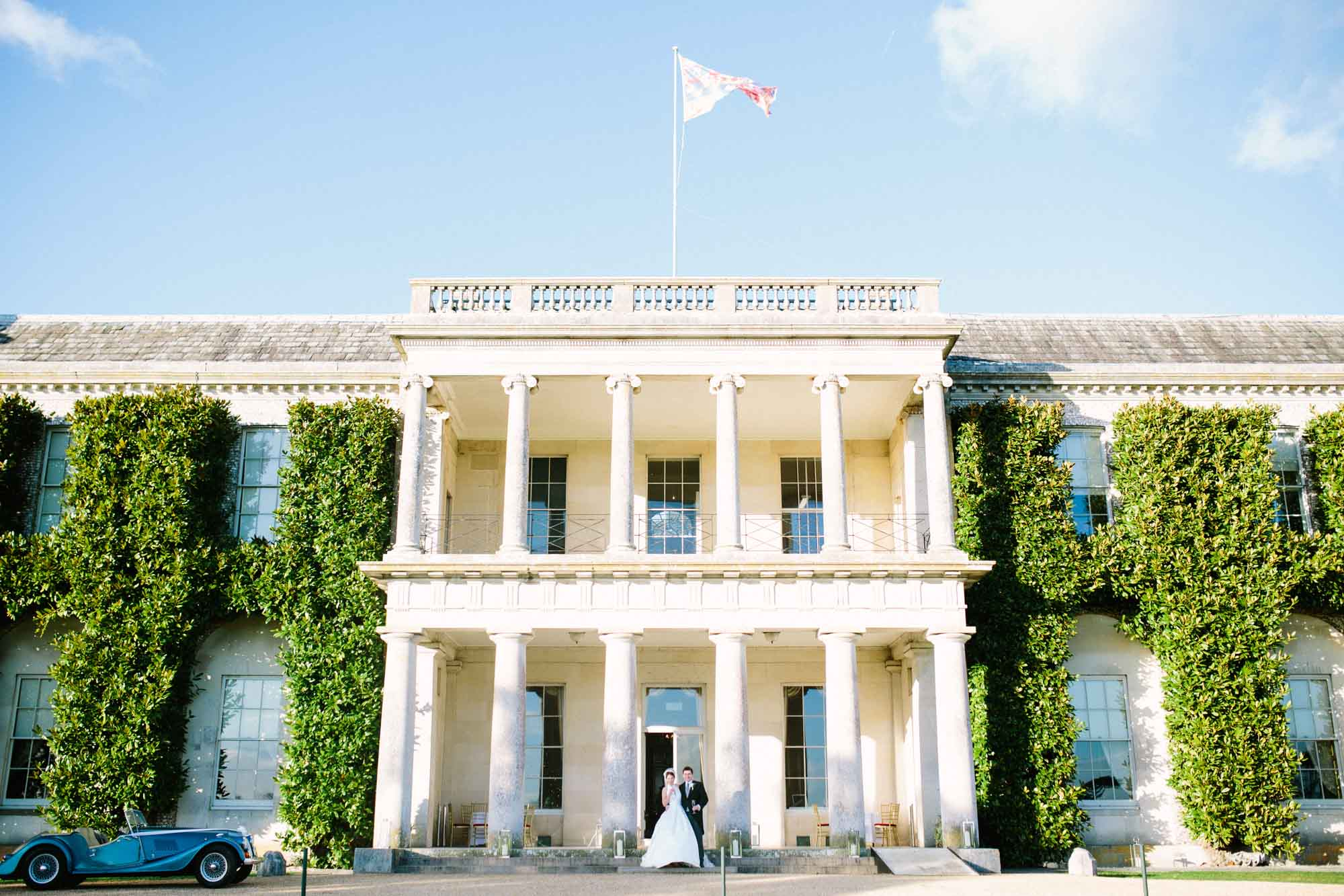 Bride and groom standing in the entrance of Goodwood House