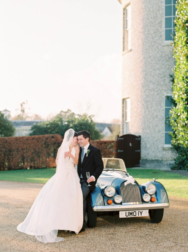 Bride and groom cuddling next to their blue convertible vintage wedding car at Goodwood House wedding
