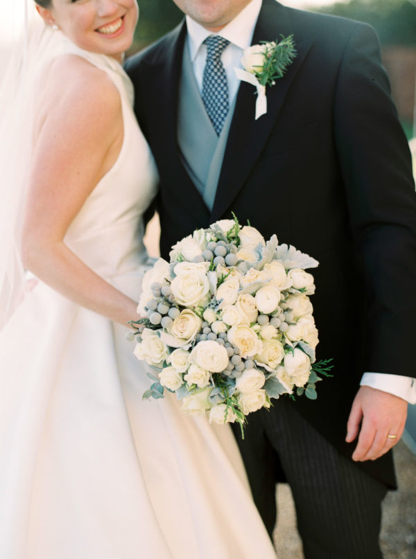 Close up photograph of white and green winter wedding bouquet with white and green