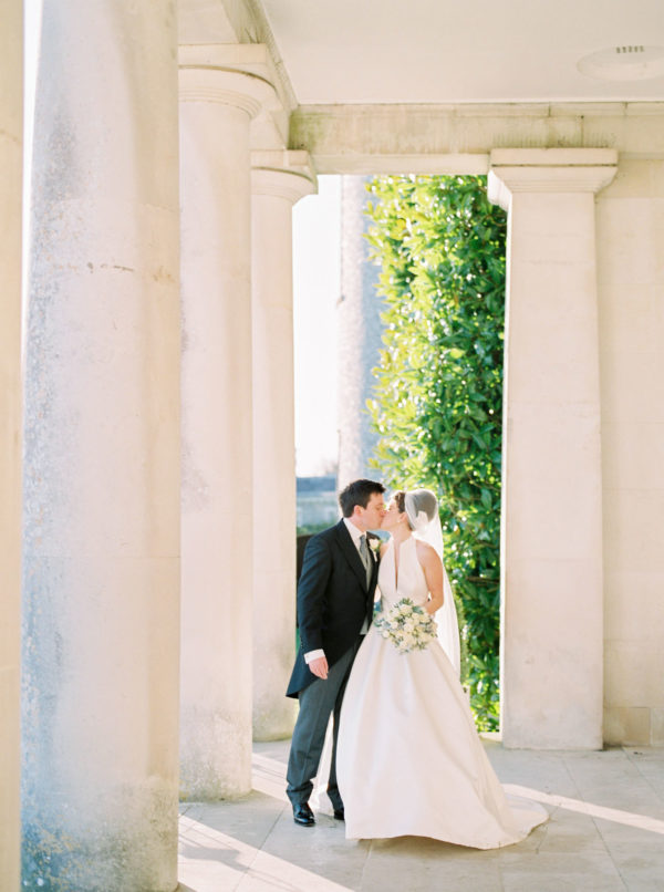 Bride and groom kissing under the pillars of Goodwood House wedding