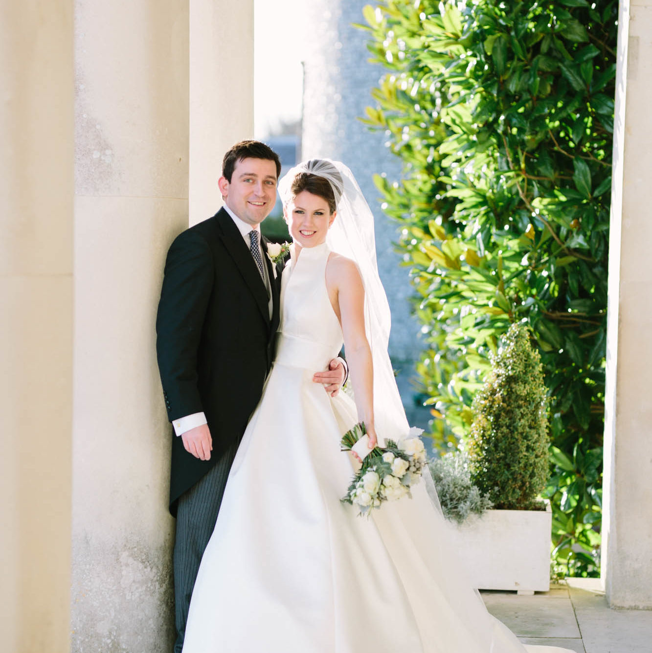 Bride and groom standing beneath the pillars of Goodwood House