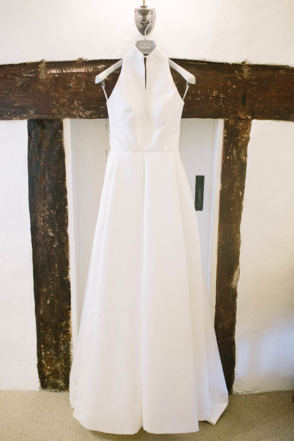 Jesus Peiro wedding dress hanging on wooden beam in bride's home