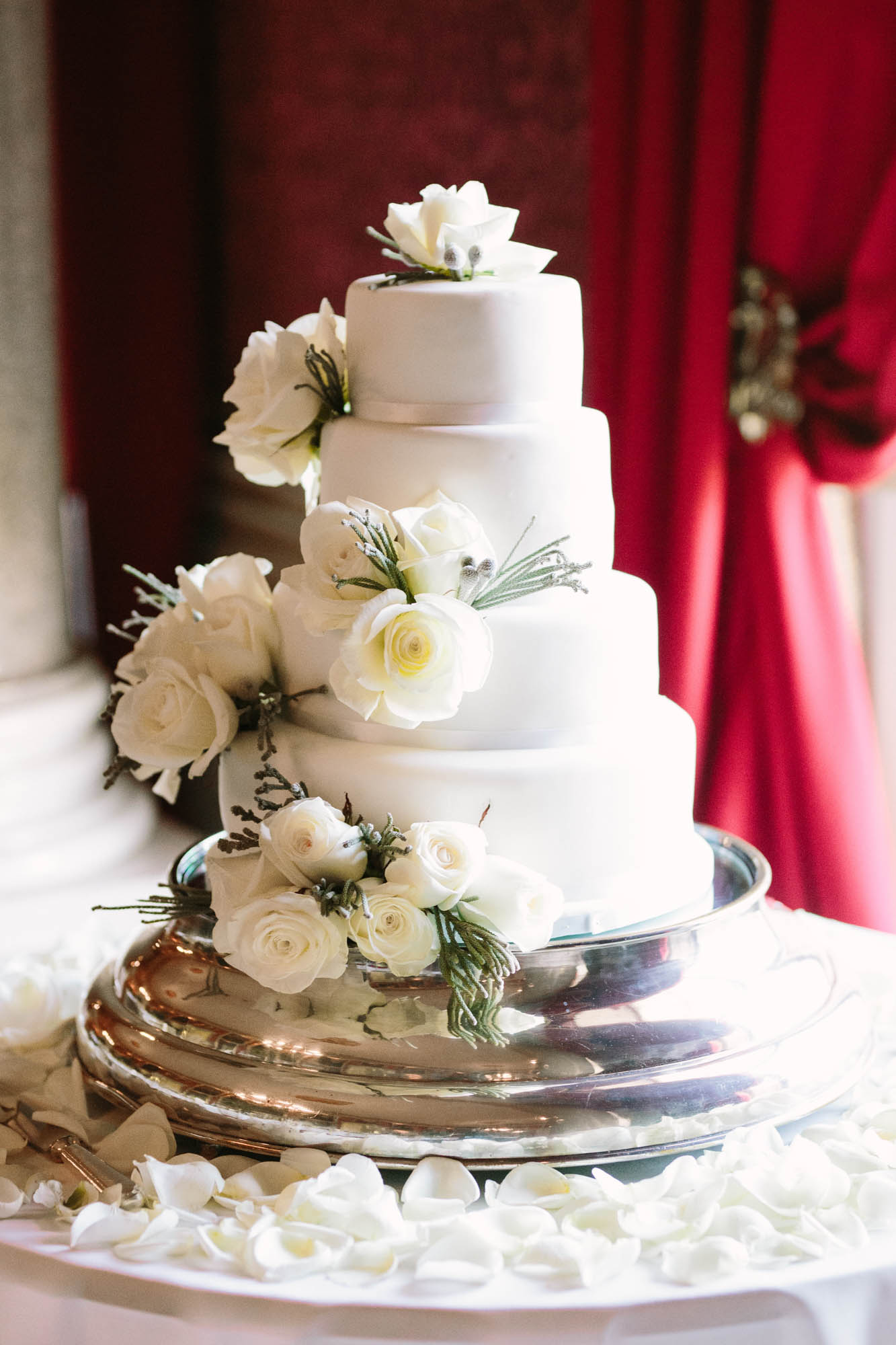 White three tier wedding cake decorated with white roses at Goodwood House