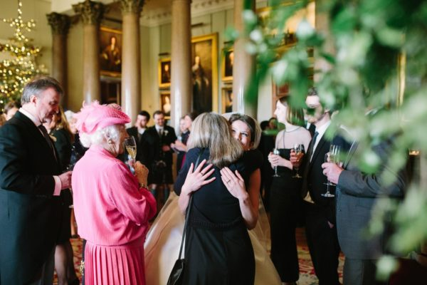 Bride hugging wedding guests at Goodwood House wedding