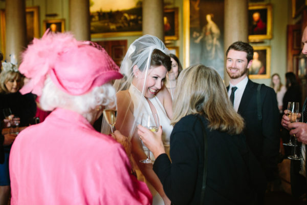 Bride smiling ay wedding guests inside Goodwood House