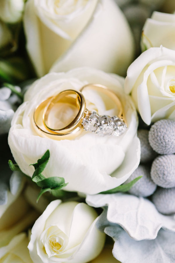 Diamond engagement ring and gold wedding bands in a rose