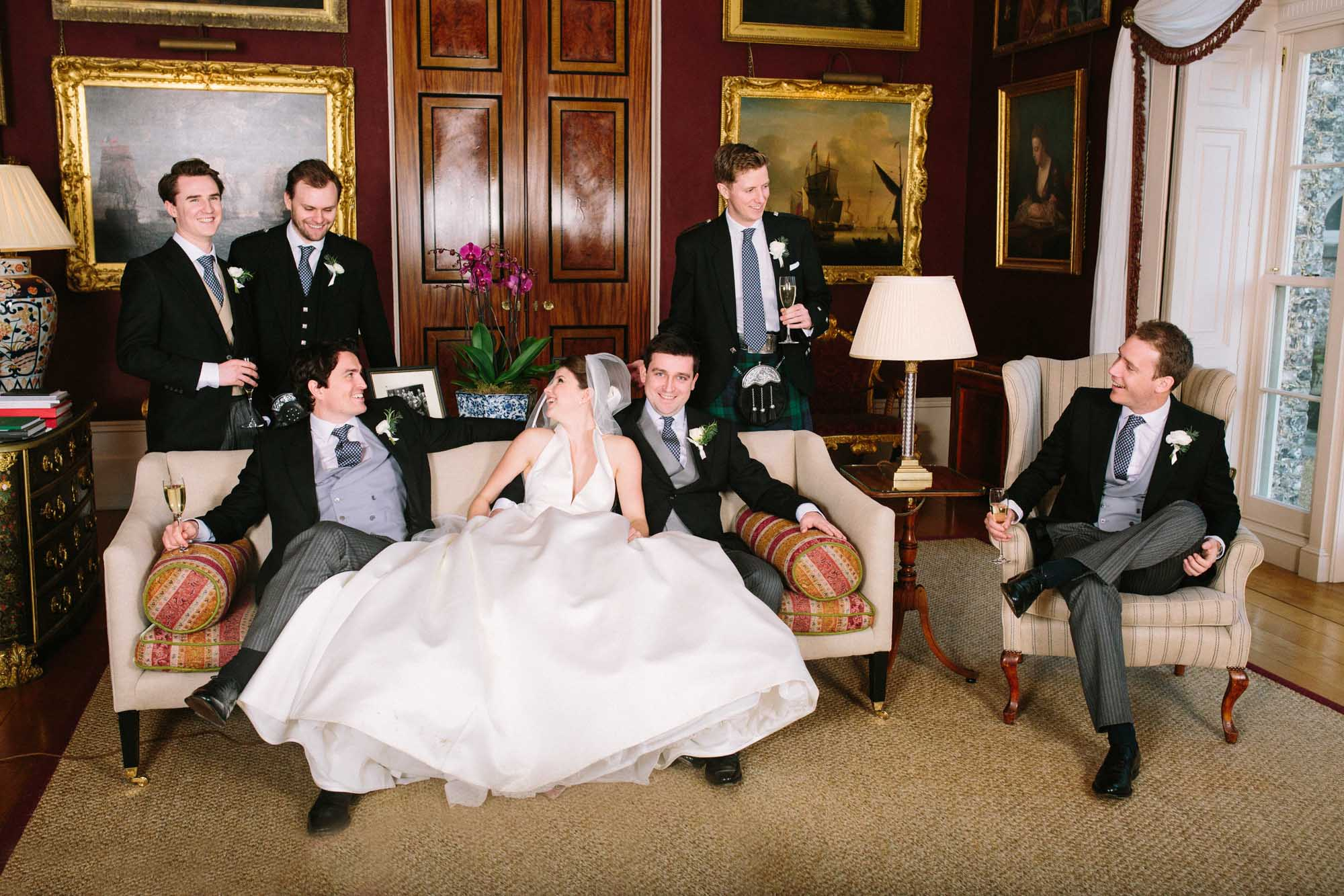 Relaxed group photo in the lounge of Goodwood House wedding