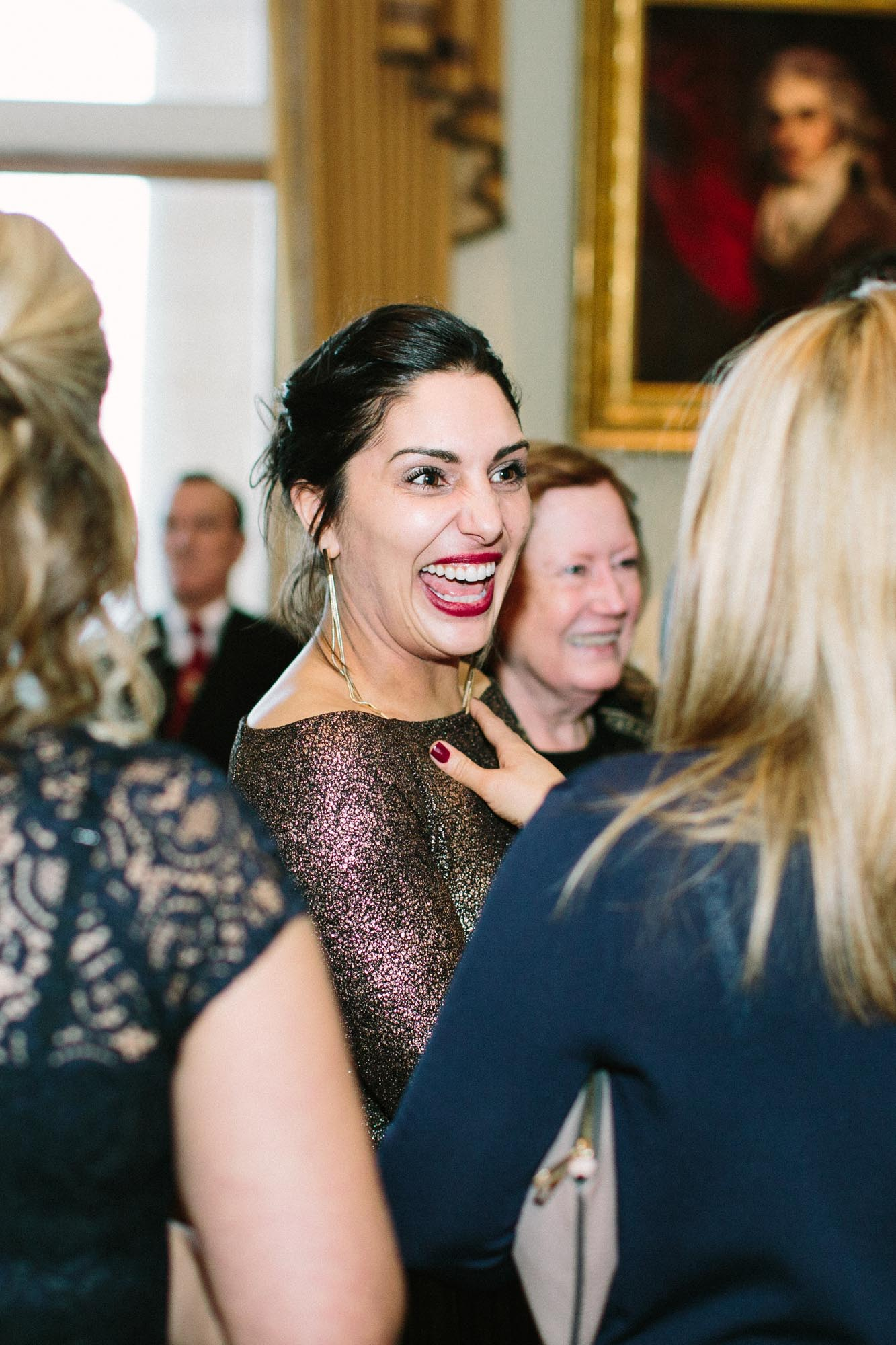 Wedding guests laughing during reception at Goodwood House wedding