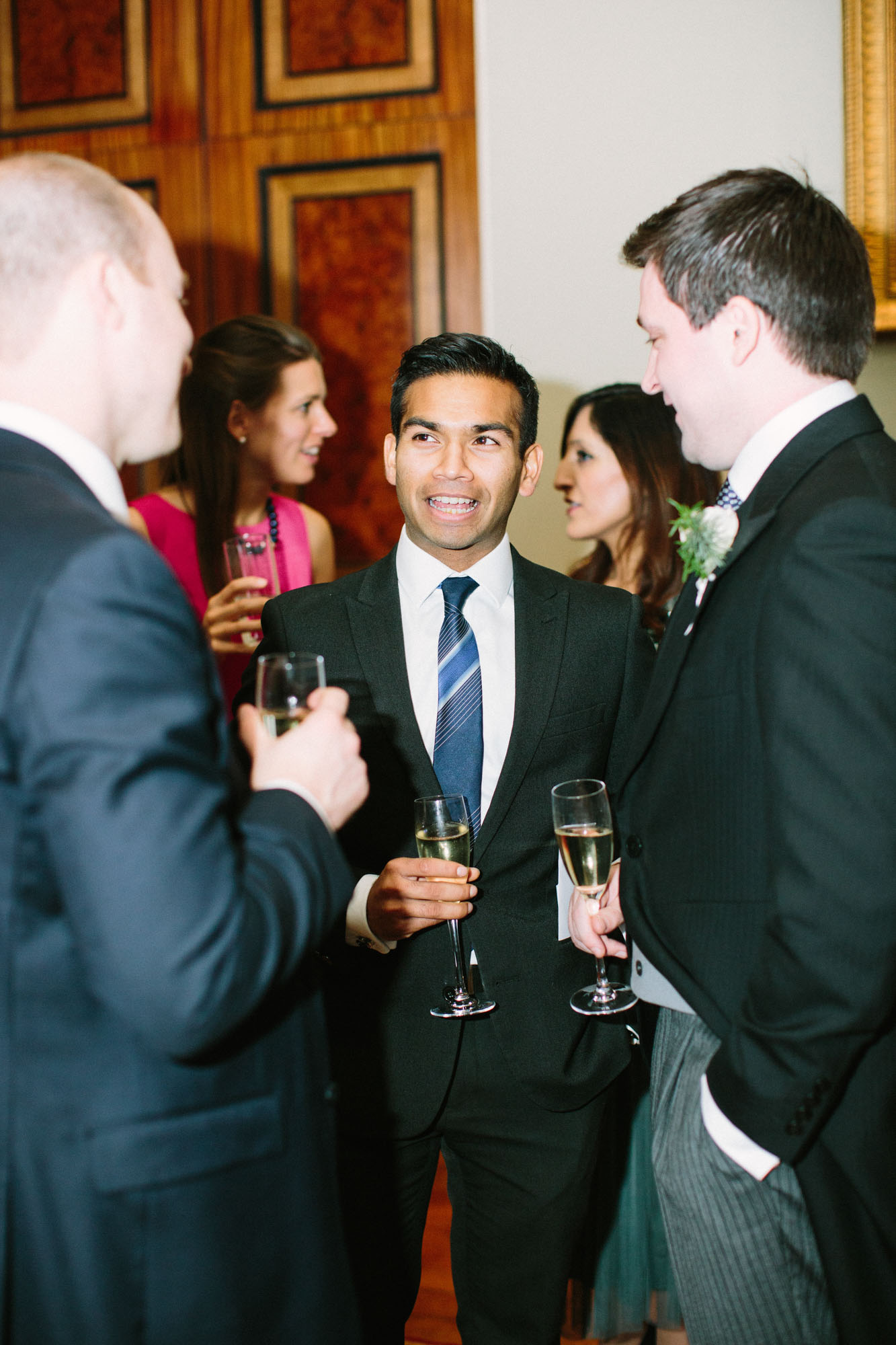 Wedding guests laughing and chatting inside Goodwood House