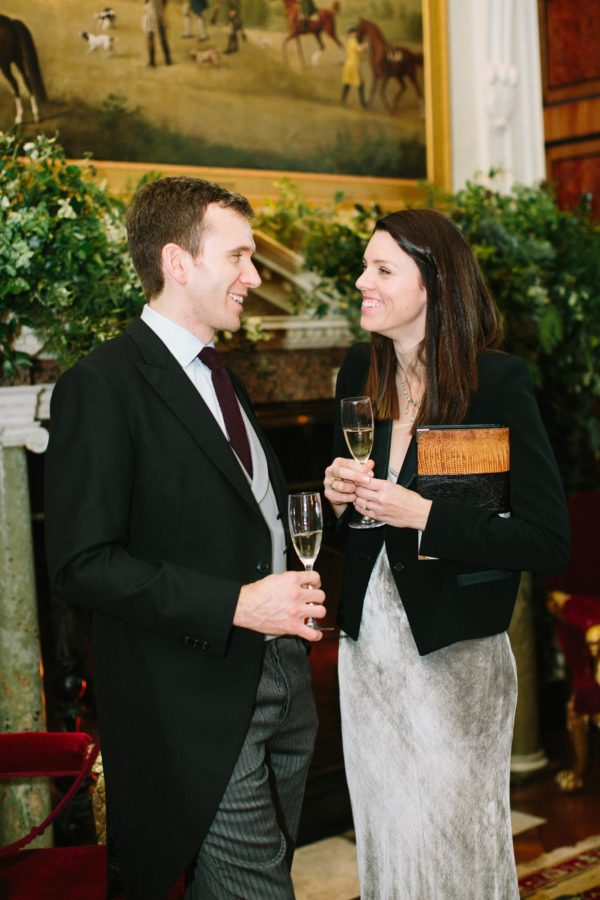 Wedding guests talking in front of fireplace at Goodwood House wedding