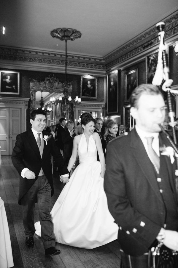 Bride and groom walking into wedding breakfast at Goodwood House wedding
