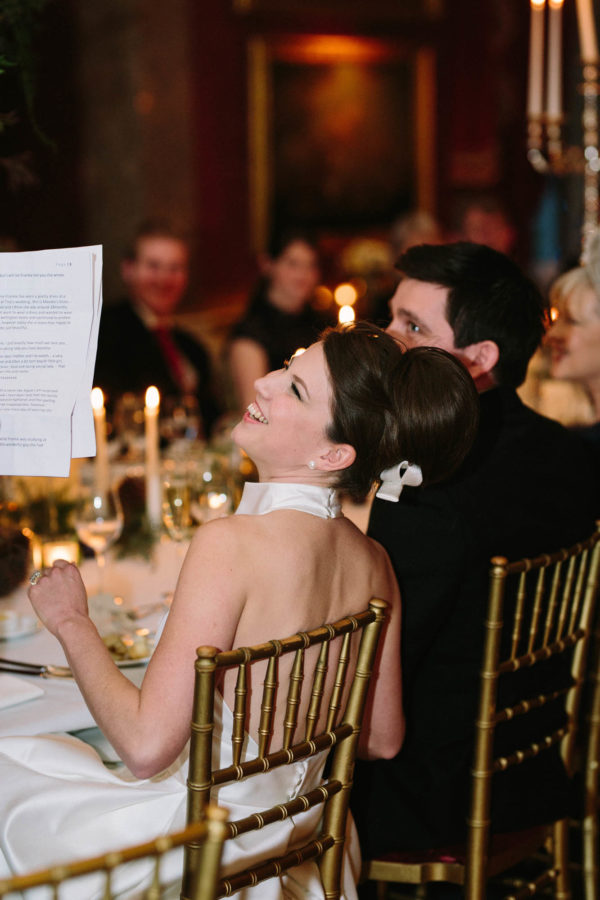 Bride laughing during speeches at Goodwood House wedding