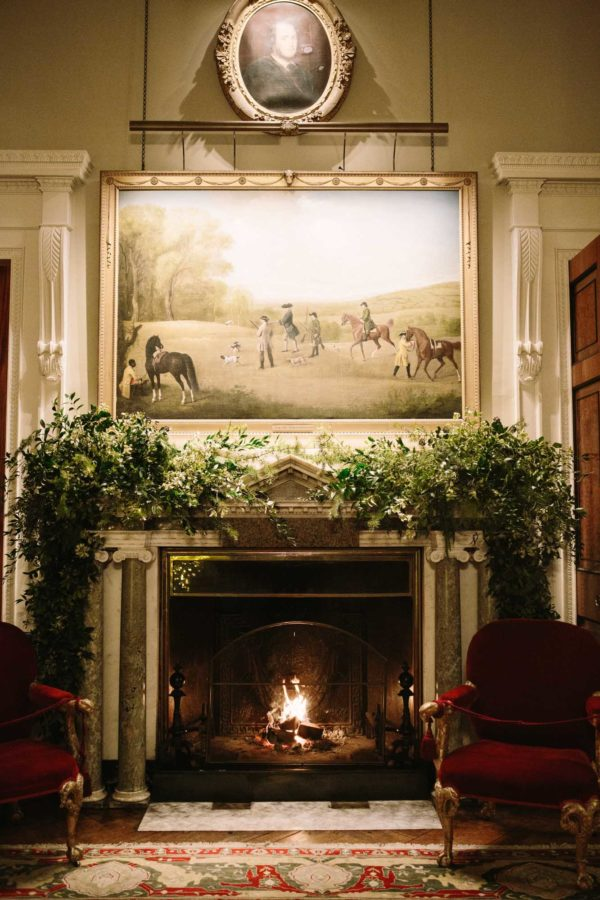 Goodwood House fireplace decorated with foliage garlands and the fire is lit