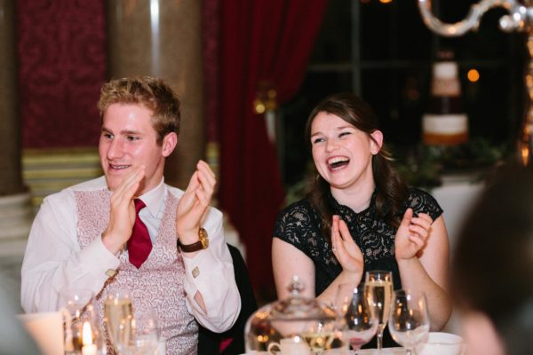 Guests laughing and clapping during speeches at Goodwood House wedding