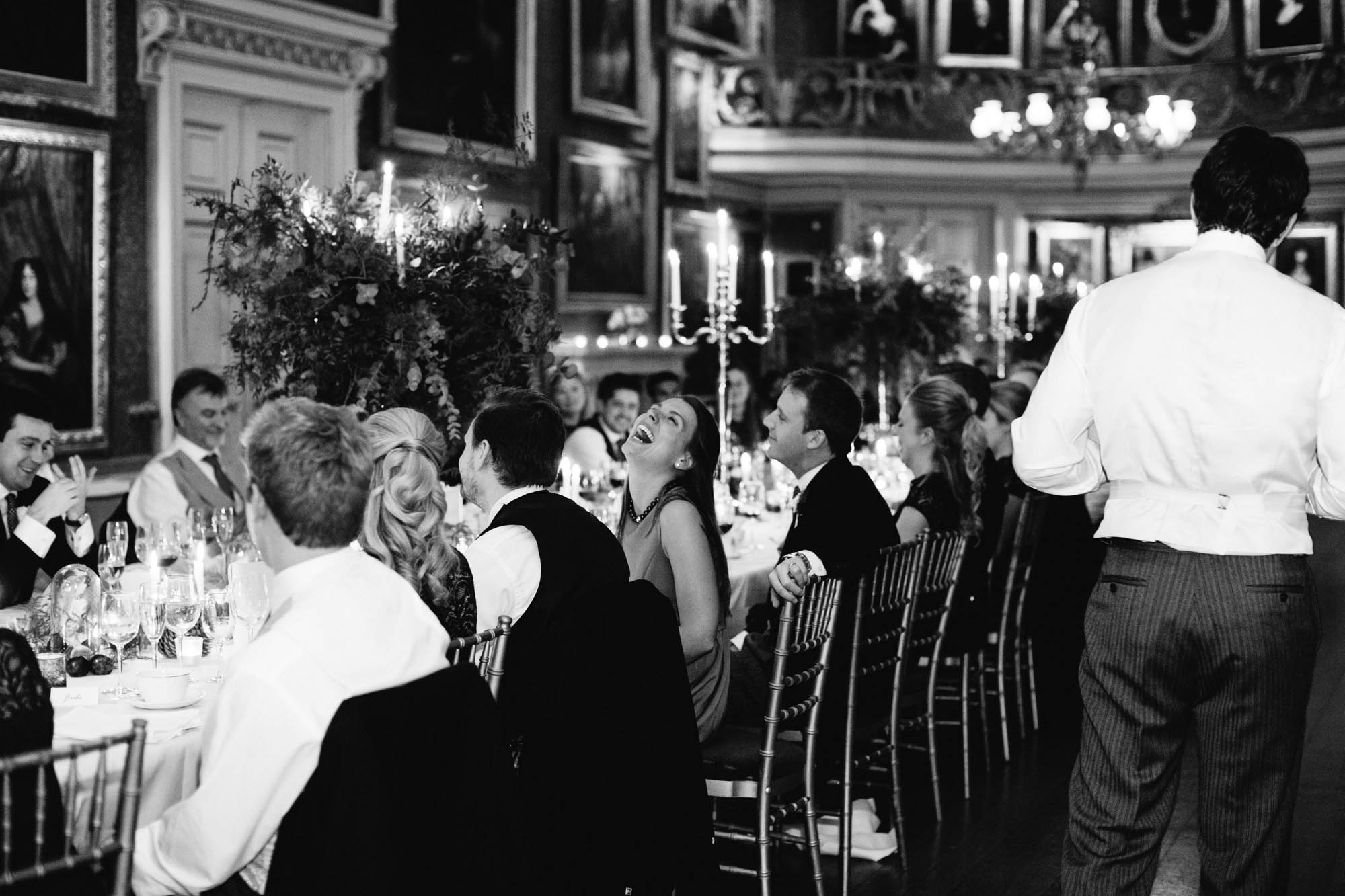 Black and white photograph of guests laughing at Goodwood House wedding