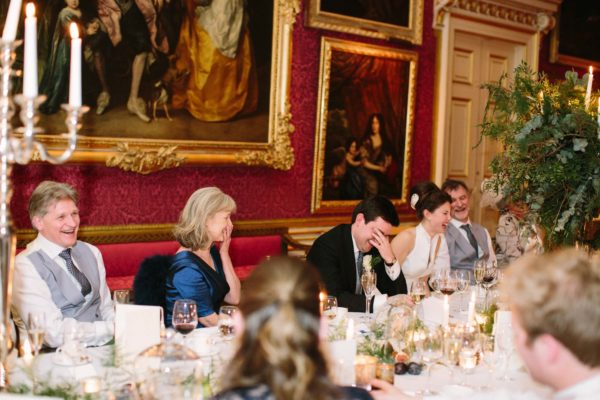 Bride with parents laughing during best man's speech at Goodwood House
