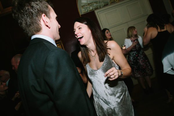 Couple dancing and laughing in the evening of a Goodwood House wedding