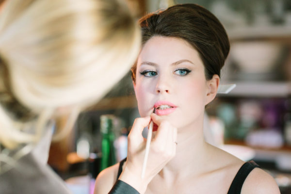 Make up artist doing bride's lipstick on morning of Goodwood House wedding