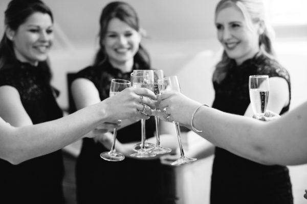 Black and white photograph of bridesmaids toasting on wedding morning