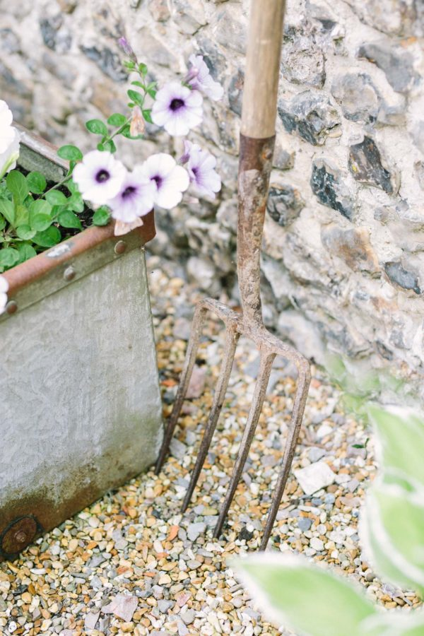Garden fork leaning against flint wall