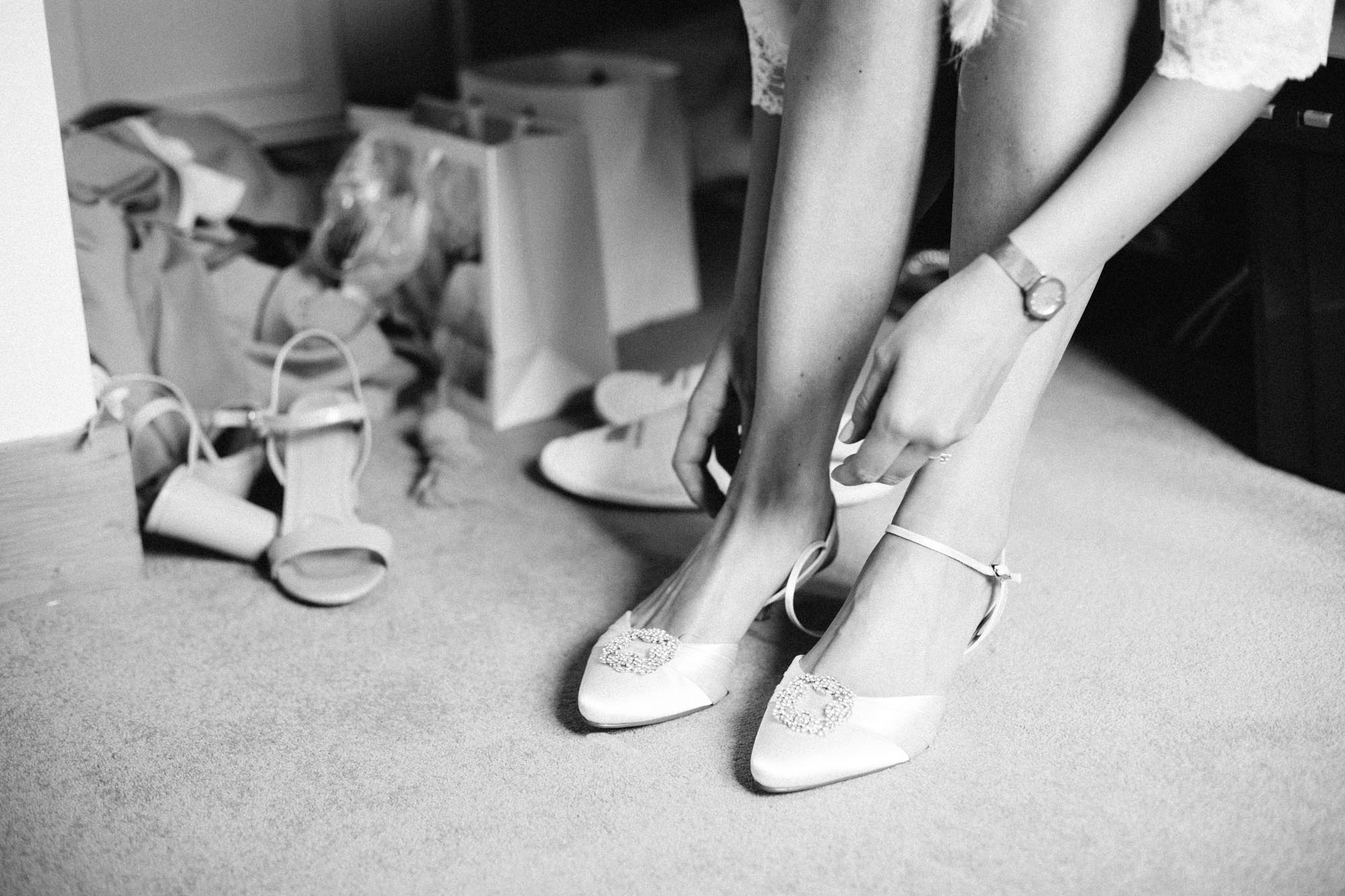 Black and white image of bride putting on her wedding shoes