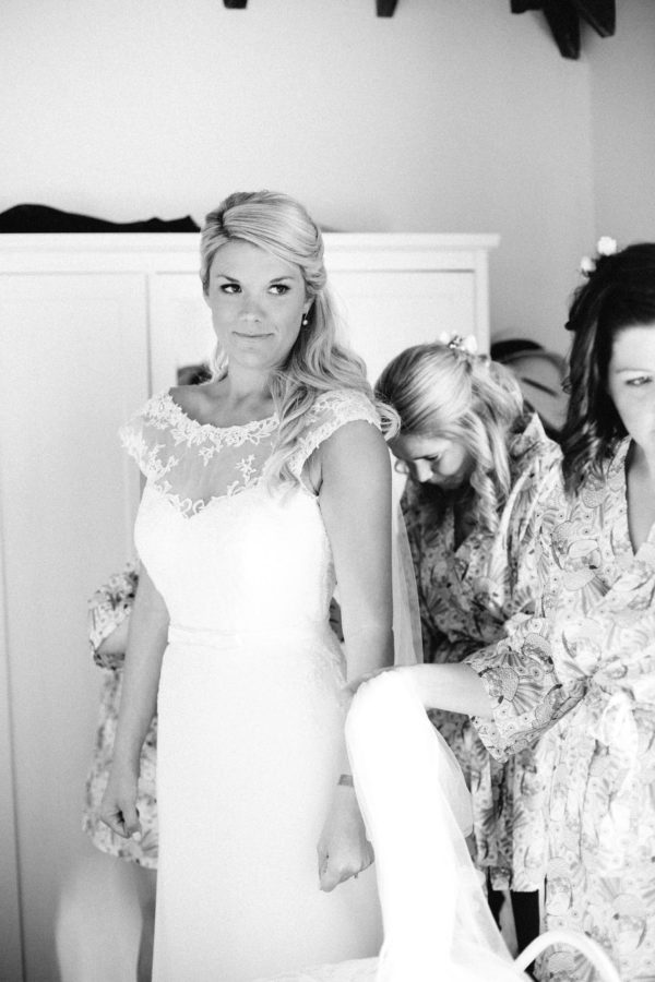 Bridesmaids doing up brides lace wedding dress