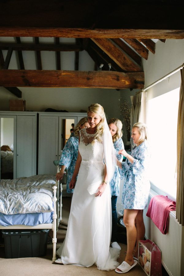 Bridesmaids helping bride put on her wedding dress