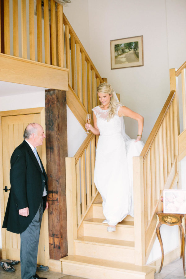 Father of the bride smiling at the bride walking down the stairs towards him