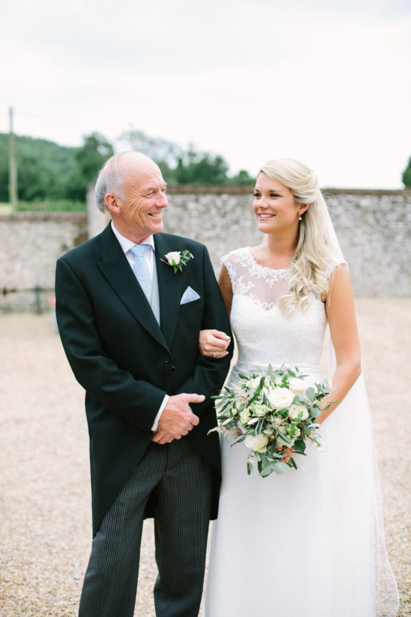 Portrait of bride and father of the bride smiling at each other