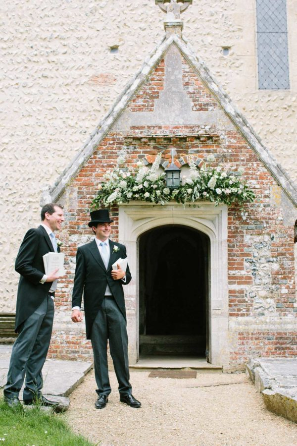 Groom and usher in top hat waiting outside church on wedding morning