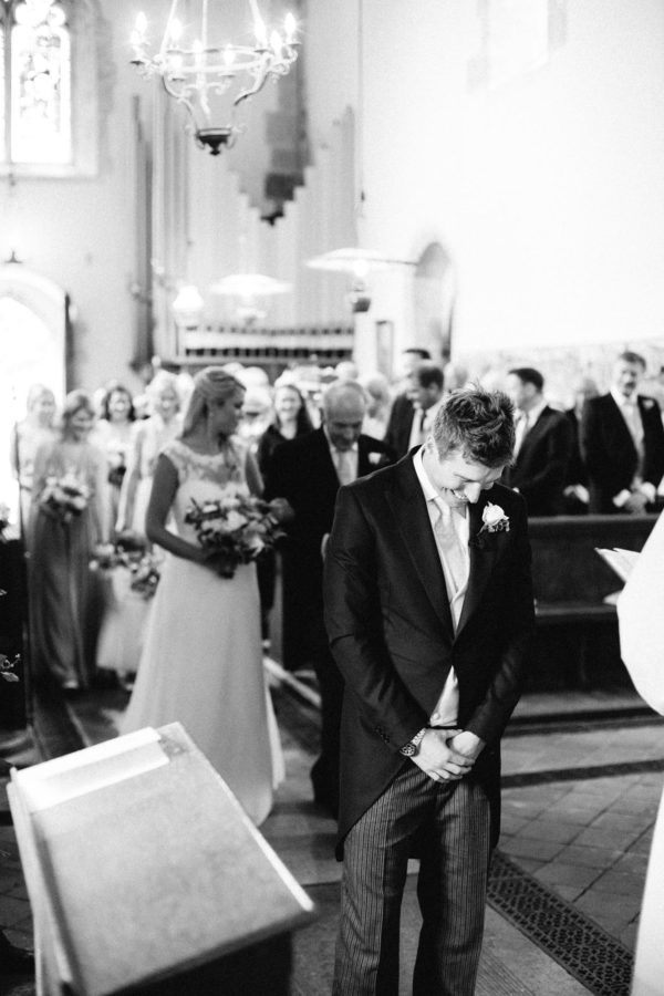 Groom waiting while bride walks up the aisle
