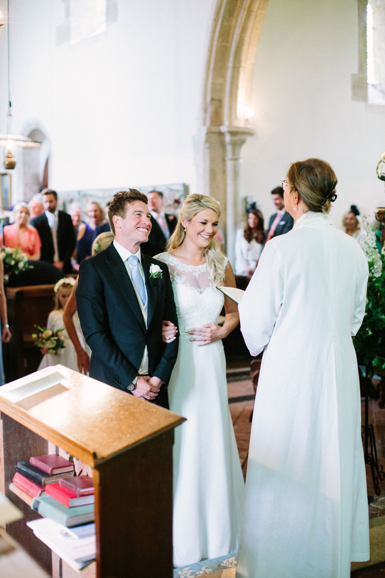 Bride and groom smiling at the front of the church during wedding ceremony