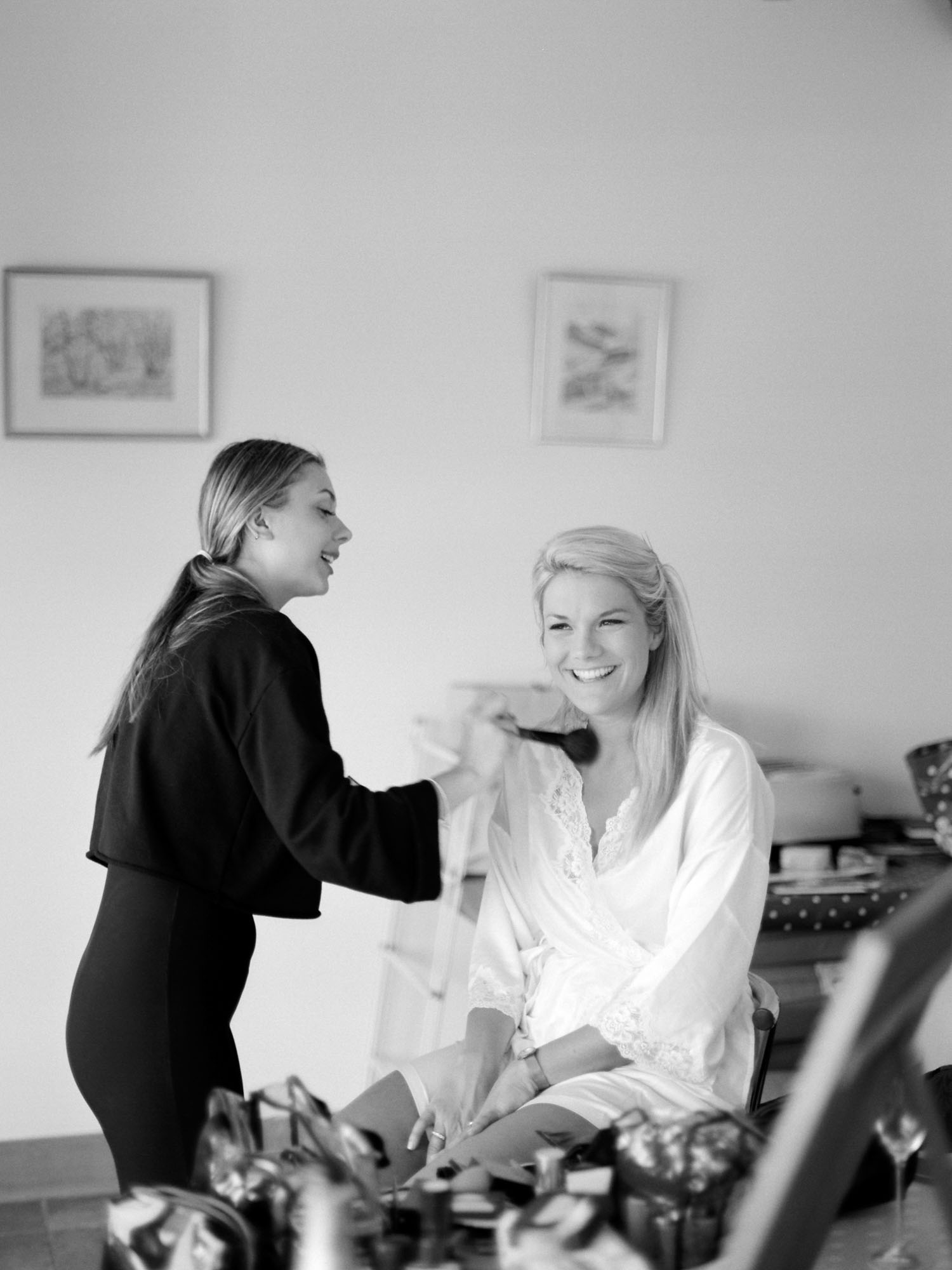 Black and white photograph of bride having her wedding make up done wearing white robe