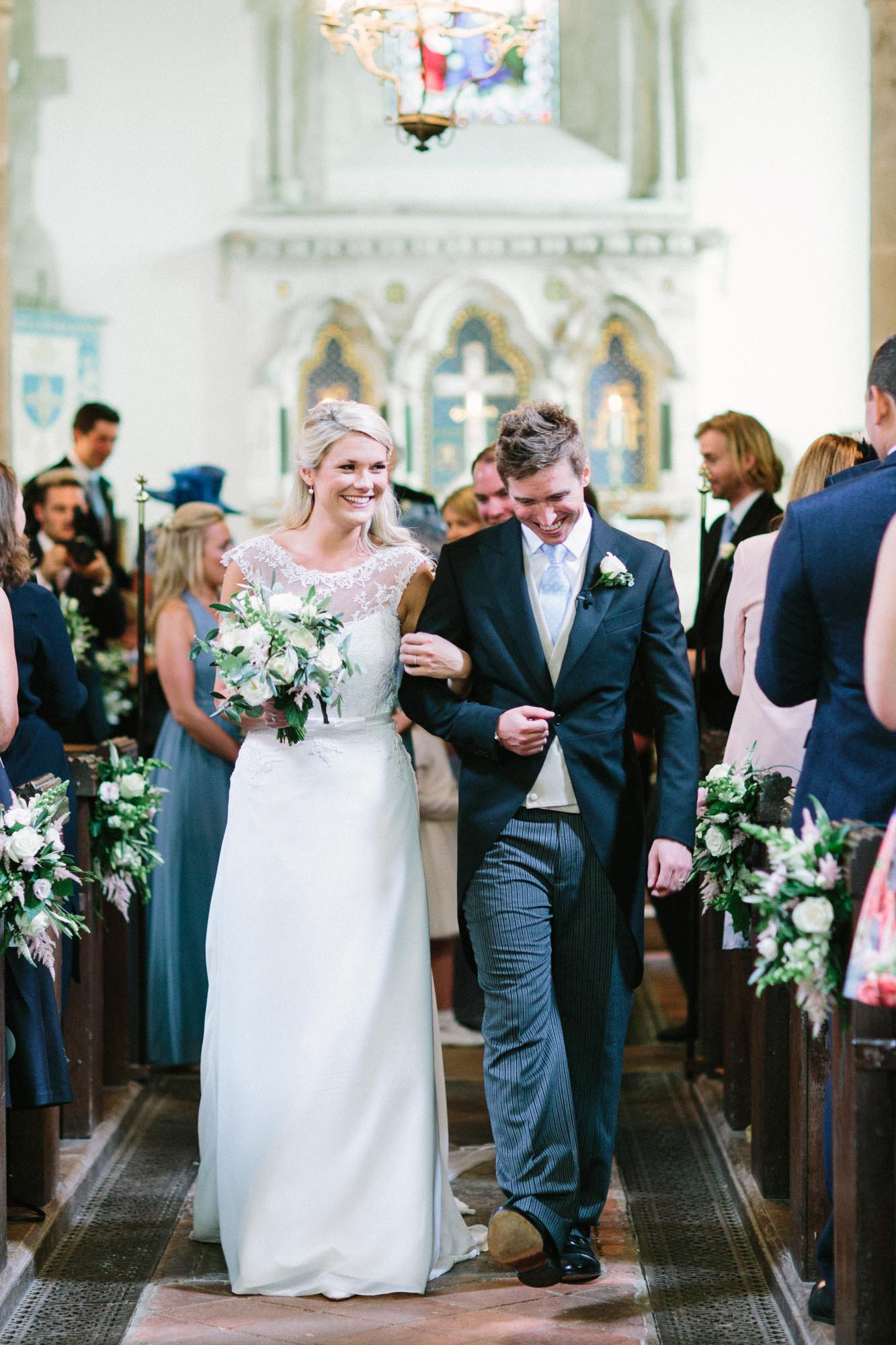 Bride and groom smiling and exiting church