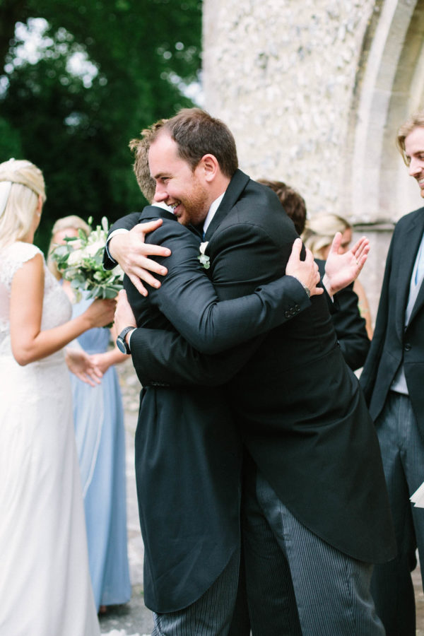Best man hugging groom just after wedding ceremony