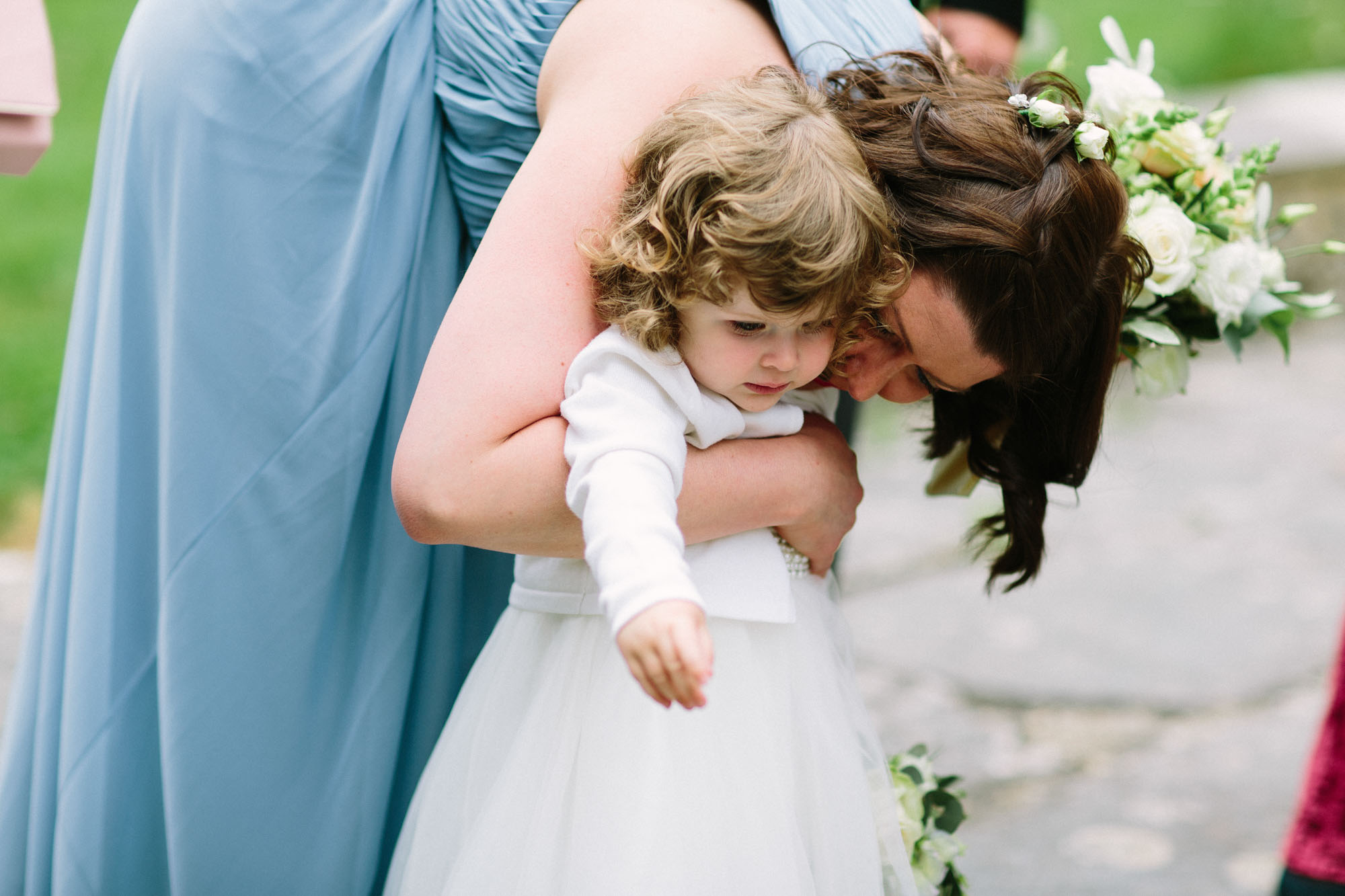 Flower girl being hugged by bridesmaid