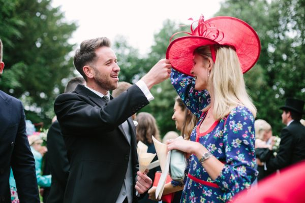 Wedding guest adjusting hat after wedding service