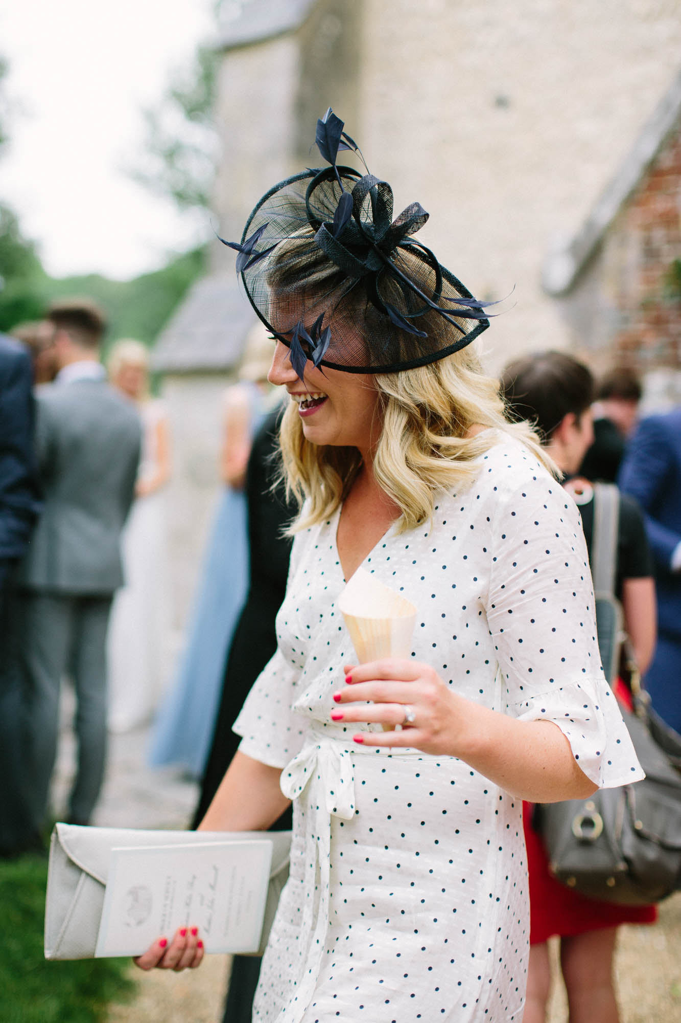 Wedding guests laughing outside church wearing black hat