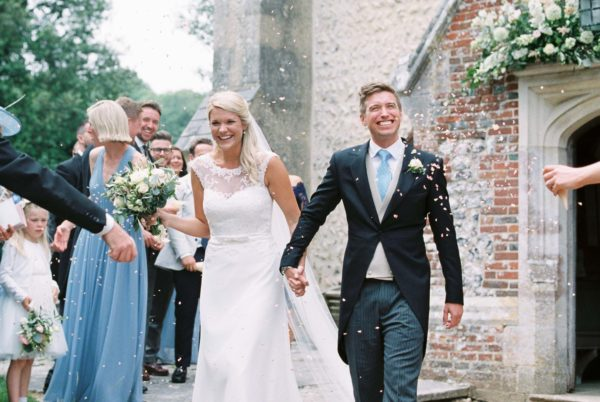 Bride and groom walking through real flower confetti and smiling